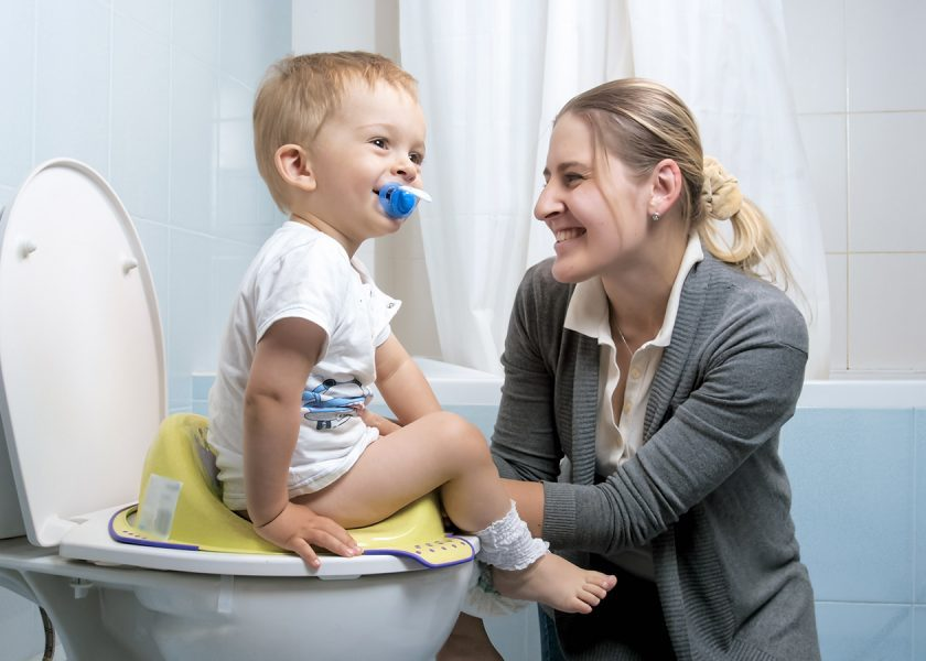 Cute little boy smiling to mother while sitting on toilet seat